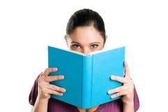 Lectura y ocultación detrás de un libro Imagen de archivo libre de regalías