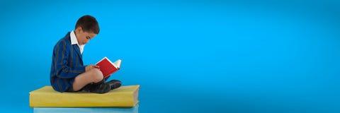 Lectura y sentada del muchacho en una pila de libros con el fondo azul Fotos de archivo libres de regalías