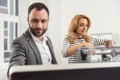 Lecture agréable d'homme à partir d'ordinateur tandis que femme lançant l'imprimante 3D Image stock