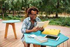 Lecture belle heureuse de jeune homme et sudying en café extérieur Photo stock