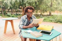 Lecture belle heureuse de jeune homme et sudying en café extérieur Photo libre de droits