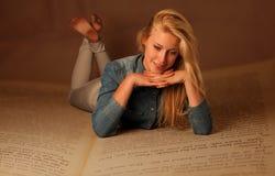 Lecture blonde d'amour d'étudiant se trouvant sur le livre énorme Photo stock