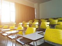 Empty lecture chair in classroom university with sun light morning Royalty Free Stock Photo
