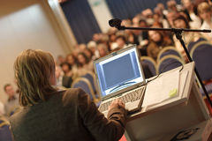 Lecture at Convention. Business woman at podium with laptop computer lecturing audience in auditorium