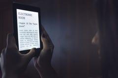 Lecture d'un ebook dans le lit Photo libre de droits