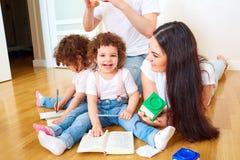 Lecture d'un livre avec votre famille Une famille heureuse Jumeaux d'enfants photos stock