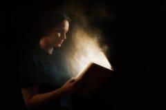 Lecture d'un livre rougeoyant image libre de droits