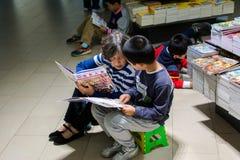 Lecture de aide de petit-fils de grand-mère dans la librairie Images stock