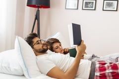 Lecture de couples dans le lit photos stock