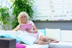 Lecture de détente de femme d'une cinquantaine d'années à la maison images stock