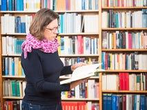 Lecture de femme devant des étagères photographie stock libre de droits