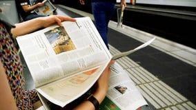 Lecture de femme en journal de métro dans le mouvement lent banque de vidéos