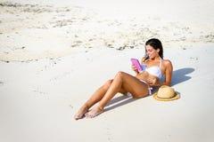 Lecture de femme sur l'eBook à la plage image stock