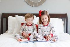 Lecture de garçon et de fille sur le lit avec des pyjamas de Noël photographie stock libre de droits