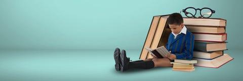 Lecture de garçon sur le plancher avec des livres sur le fond gris Photo libre de droits