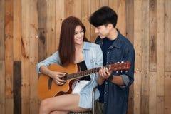 Lecture de jeune fille et guitare de jeu Photos libres de droits