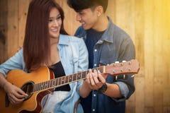 Lecture de jeune fille et guitare de jeu Photographie stock libre de droits