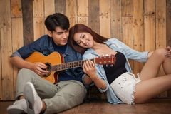 Lecture de jeune fille et guitare de jeu Images stock