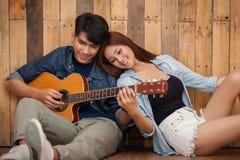 Lecture de jeune fille et guitare de jeu Images libres de droits