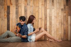 Lecture de jeune fille et guitare de jeu Photos stock