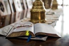 Lecture de la bible avec des verres de lecture Photographie stock