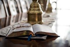 Lecture de la bible avec des verres de lecture Photos stock