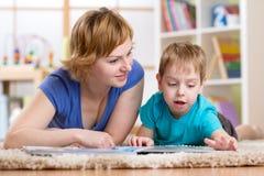 Lecture de maman et de fils sur le tapis dans la chambre Images libres de droits