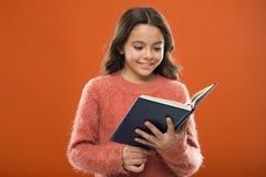 Lecture des activités pour des enfants Le livre de prise de fille a lu l'histoire au-dessus du fond orange L'enfant apprécient le photographie stock