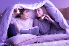 Lecture heureuse de maman et de fille sous la couverture avec des torches Images stock