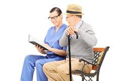 Lecture professionnelle de soins de santé masculins au monsieur supérieur assis Photos stock