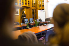 Lecture at university. Speaker giving presentation in lecture hall at university. Female PhD candidate defending her doctoral thesis in front of the committee Royalty Free Stock Images