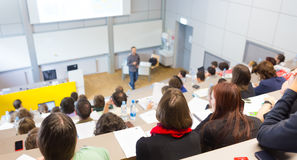 Lecture at university. Speaker giving presentation in lecture hall at university. Students listening to lecture and making notes Royalty Free Stock Photos