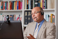 Lecturer with computer, camera and headset Royalty Free Stock Images