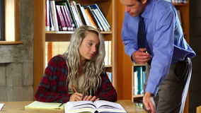 Lecturer helping blonde student in the library stock video