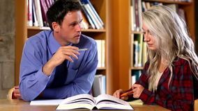 Lecturer helping his confused student in the library stock video footage