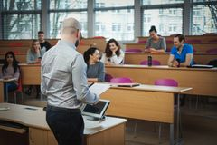 Lecturer and multinational group of students in an auditorium royalty free stock images