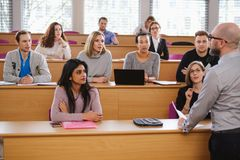 Lecturer and multinational group of students in an auditorium stock image