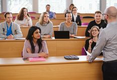 Lecturer and multinational group of students in an auditorium stock images