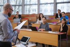 Lecturer and multinational group of students in an auditorium royalty free stock photography