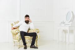Lecturer sit on armchair and holds book, white wall background. Scientist, professor on thoughtful face analyzing. Literature. Man with beard and mustache royalty free stock images