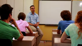 Lecturer sitting and speaking to his students in classroom stock video footage