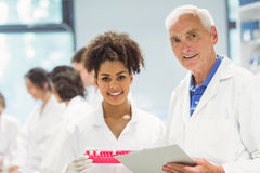 Lecturer and student smiling at camera in the lab Stock Images