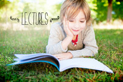 Lectures against cute little boy reading in park Stock Images