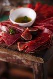 Leczący oliwa z oliwek na textured starej drewnianej stolec i mięso Obrazy Stock