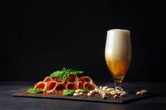 Leczący prosciutto z basilem i czara alkoholiczny piwo z pianą na czarnym tle Słone dokrętki, smakowici baleronów plasterki i A obraz royalty free