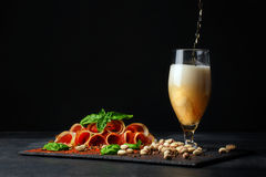Leczący prosciutto z basilem i czara alkoholiczny piwo z pianą na czarnym tle Słone dokrętki, smakowici baleronów plasterki i A zdjęcie stock
