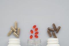 Leczniczy kapsuła upadek z trzy klingerytów butelek na ligh Zdjęcia Stock