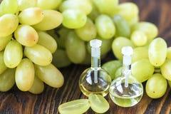 Leczniczy winogron ziaren olej w szklanym słoju, świezi winogrona na starym drewnianym tle, nasieniodajny ekstrakt przeciwutlenia Obrazy Royalty Free