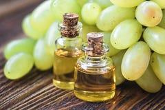 Leczniczy winogron ziaren olej w szklanym słoju, świezi winogrona na starym drewnianym tle, nasieniodajny ekstrakt przeciwutlenia Zdjęcie Stock
