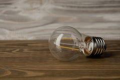 LED力量灯电电灯泡木头背景 库存照片